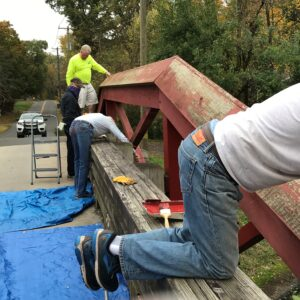 Volunteers paint a camelback bridge. bridge.